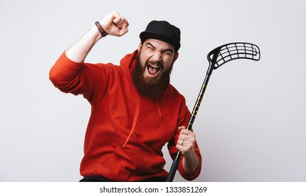 Floorball concept, exited bearded man in red hoody holding stick and doing win gesture with rised hand over white background