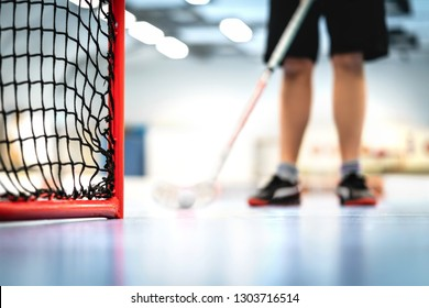Floorball goal and net. Player training in the background. Man playing floor hockey on court.