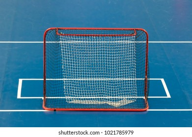 Floorball goal on blue rink with clear white lines. Red metallic construction with synthetic net.