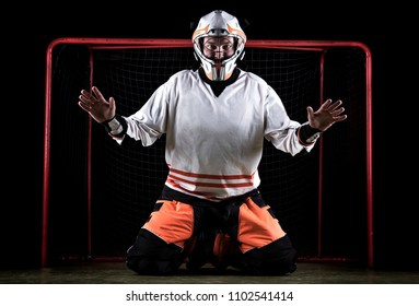 Floorball goalkeeper is in catching position with helmet on.