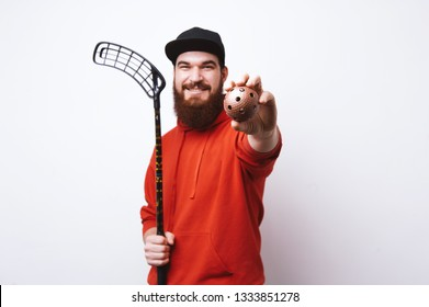 A floorball  player, bearde man in red hoody, holding stick while showing a ball at camera