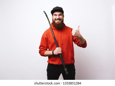Floorball player, bearded man in red hoody holding floorball stick and dooing like gesture against  white background