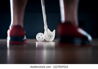 Floorball player standing with stick and ball on. Floor hockey. Back view between sneakers. Dramatic light.