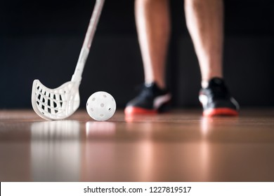 Floorball player standing with white ball and stick. Floor hockey concept.