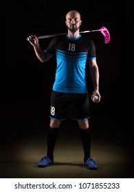 Floorball player with a stick and a ball standing, studio photography