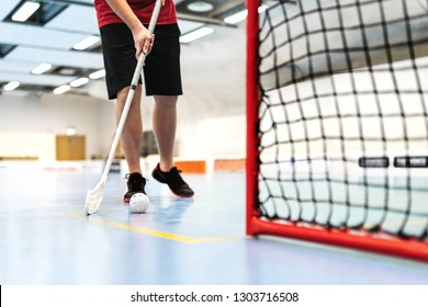 Floorball player training on court. Floor hockey concept. Man running with stick and ball in arena. Scoring goal.