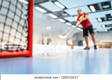 Floorball training on court. Man training floor hockey in arena. Slap shot on goal.