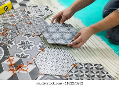 flooring - man laying hexagon tiles on the floor