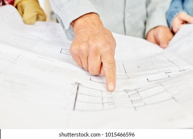 Floorplan and architect pointing and making decisions about building construction