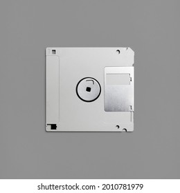 Floppy disk on gray paper background. Gray diskette. Top view. Flat lay.