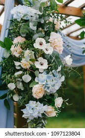 Floral arch with blue cloth and wooden elements at a rustic  wedding ceremony