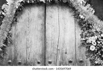 Floral archway on old wooden door with copy space in stunning black and white