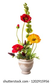 Floral arrangement from artificial poppy flowers in old ceramic flower pot isolated on white background.