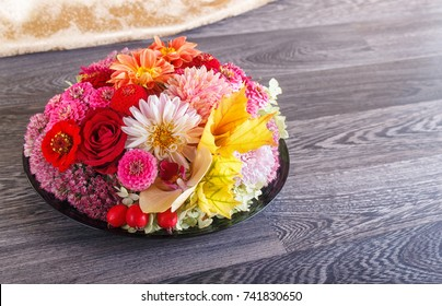 floral arrangement of autumn flowers on a plate. dahlia, zinnia, rose, orchid, maple leaves. copy space.