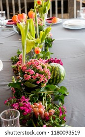 A floral arrangement of lovely orange flowers with colourful pink bunch in foreground with an enticing round watermelon & grapes. A party and with a red serviette and glass crockery and plate. Lovely