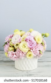 Floral arrangement with pink carnation and yellow eustoma flowers.