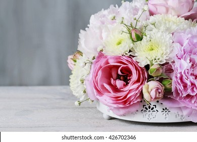 Floral arrangement with pink peonies, tiny roses, chrysanthemums and gypsophila paniculata twigs, copy space.