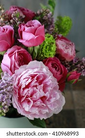 Floral arrangement with pink roses, peonies and lilacs.