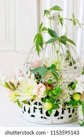 Floral arrangement with roses, dahlias and iris flowers inside a vintage bird cage.