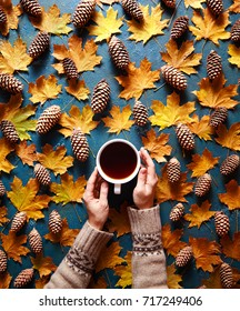 Floral autumn background. A mug of coffee in a woman's hands in a sweater on the green background with yellow maple leaves and cones. Hello autumn mood. Flat lay instagram fashion drink composition.