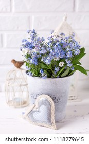 Floral background - blue forget-me-nots or myosotis flowers   in grey bucket, heart  and  candles in lanterns on  white wooden background. Floral still life.  Selective focus. Vertical image.