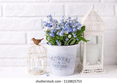 Floral background - blue forget-me-nots or myosotis flowers   in grey bucket and  candles in lanterns on  white wooden background. Floral still life.  Selective focus. Place for text.