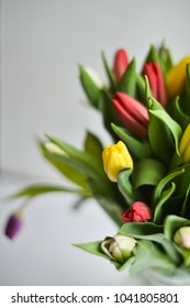 Floral background: bouquet of multicolored tulips in a glass vase on a light background, blank, mocap for mother's day greetings, international women's day