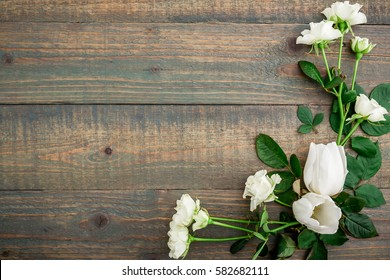 Floral background. Floral frame made of white flowers and green leaves isolated on wood background. Flat lay, top view.