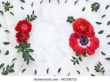 Floral background and frame with red flowers on marble.  Top view