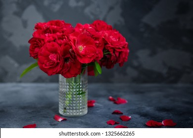 Floral background, wallpaper, greeting card image. Bouquet of red roses in glass vase on dark grey concrete background. Copy space.