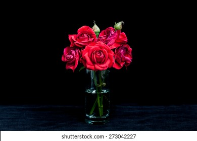 Floral background, wallpaper, greeting card image. Bouquet of red roses in glass vase on  black velvet texture.