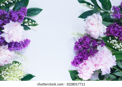 Floral borders of fresh flowers - lilac, peonies and lilly of the walley fresh flowers on white background with copy space