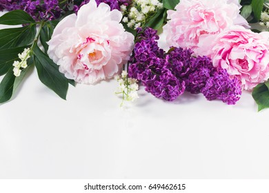 Floral borders of fresh flowers - lilac, peonies and lilly of the valley flowers on white background