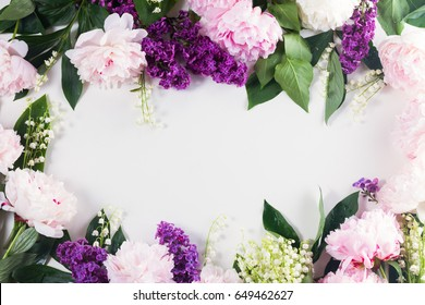 Floral borders of fresh flowers - lilac, peonies and lilly of the valley flowers frame on white background with copy space