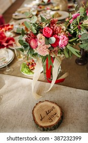 "Floral and candle wedding decoration on festive  table with sign ""I love you"" on wooden stand"