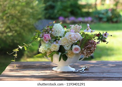 Floral composition, beauty bouquet in antique faience vase, rustic secateurs, scissors on aged table, outdoor and space, vintage style, daylight