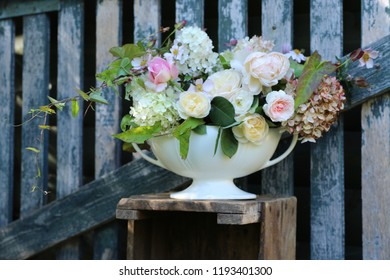 Floral composition, beauty bouquet in antique faience vase on aged wooden fence, outdoor and space, vintage style, daylight