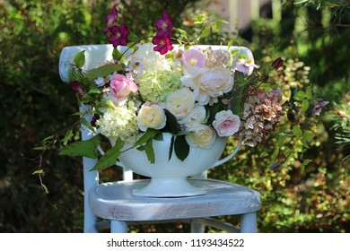 Floral composition, beauty bouquet in antique faience vase on aged wooden chair, outdoor and space, vintage style, daylight