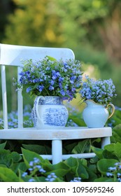 Floral composition with flowers in vintage porcelain and faience pitcher on aged wooden chair on garden background, outdoor and space, daylight, vertical photo