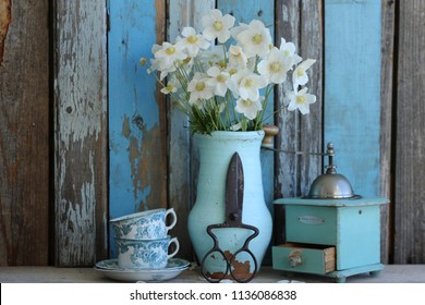 Floral composition with fresh bouquet of anemones in old authentic aged pot, vase, rustic scissors, pair of antique china cups, vintage manual coffee grinder mill on weathered wooden background