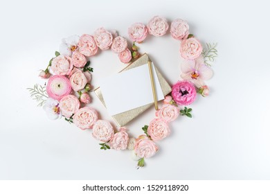 Floral composition. Heart frame made of pink rose and ranunculus flowers on white background. Flat lay, top view, copy space on card