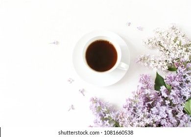 Floral composition made of beautiful purple lilac, syringa flowers on white wooden background with cup of coffee. Feminine office desk, styled stock image, flat lay, top view with empty space.