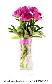 Floral composition with pink peonies in glass vase isolated on white