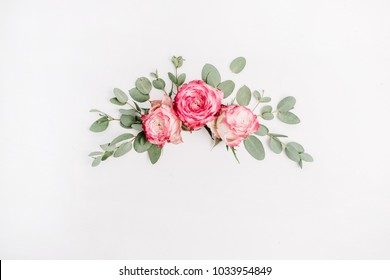 Floral composition with pink rose flower buds and eucalyptus on white background. Flat lay, top view.