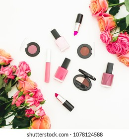 Floral composition with roses, buds, green leaves and feminine cosmetics on white background. Flat lay, top view. Spring background