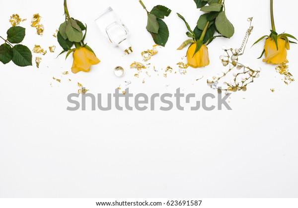 Floral composition with yellow roses. female accessories and green leaves on white background. Space for text, flatlay, top view. mockup. Header for blog