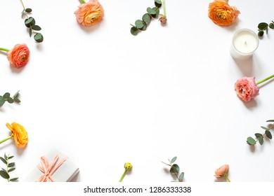 Floral concept frame on the with background  with a gift and a candle. Top view Mothers day or Womens day card. Copy space