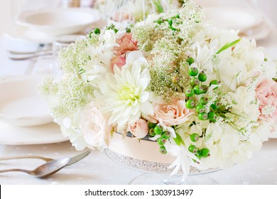 Floral decorations on summer party table. Centerpiece with rose, dahlia and hortensia flowers. White plates, table cloth, romantic wedding reception.