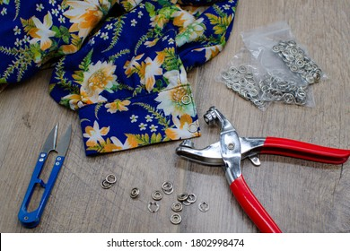 Floral fabric clothing and button fitting tools on wood background