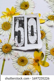 A floral fiftieth birthday card image . A stamped number fifty on white paper framed by pressed daisies and yellow winter aconite flowers